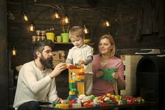 Educational game concept. Parents and their son playing with plastic blocks. Mom helping her son and husband building a. Tower out of colordul bricks royalty free stock image