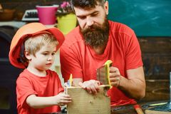 Educational games concept. Father, parent with beard teaching little son to sawing while son play with toy saw. Boy. Child busy in protective helmet learning stock image