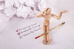 Educational goals checklist jointed doll hand ion head crumbled up paper in background. Education goals checklist wooden jointed doll hand on head start my royalty free stock photos