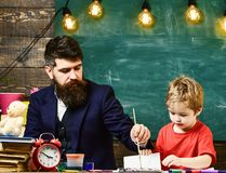Educational leisure activity. Lovely boy and father making a picture together at the table.  stock photos