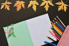 Educational tools such as notebook, pen pencils, etc on a dark background with autumn leaves. copyspace. royalty free stock photo
