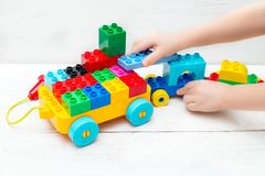 Educational toys. The child plays with the Lego designer. Flat lay Royalty Free Stock Photos