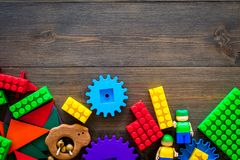 Educational toys for children mockup. Plastic blocks and clacks on dark wooden background top view space for text stock photos