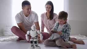 Educational toys, modern child plays automated robot on remote control of smartphone with mum and dad sitting on floor. At room stock video footage