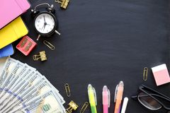 Investing time and money into education concept. Different school supplies, banknotes. Top view, close up. stock images