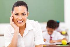 Educator in classroom. Pretty female elementary school educator siting in classroom Royalty Free Stock Photography