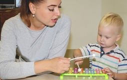 The educator deals with the child in the kindergarten. Creativity and development of the child stock image