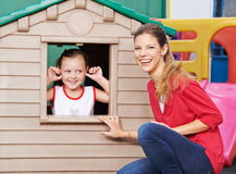 Educator with girl in playhouse in kindergarten. Happy educator playing with girl in playhouse in kindergarten Royalty Free Stock Photos