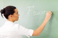 Educator sex education. Female high school educator writing sex education on chalkboard Royalty Free Stock Photos