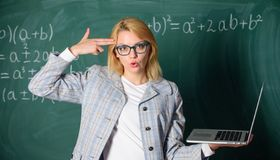 Educator smart clever lady with modern laptop hold gun gesture at her head chalkboard background. Tired teacher annoyed royalty free stock photography