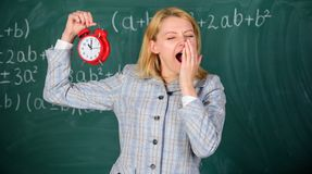 Educator start lesson. She cares about discipline. Woman teacher hold alarm clock. Girl school lecturer. What time is it. Lessons schedule. Welcome teacher royalty free stock photos