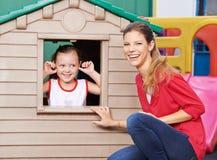 Educatore con la ragazza in casetta per giocare nell'asilo Fotografie Stock Libere da Diritti