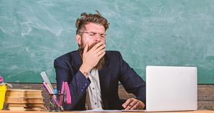 Educators more stressed at work than average people. High level fatigue. Exhausting work in school causes fatigue. Educator bearded man yawning face tired at stock photo