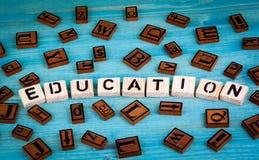 Edukaci słowo pisać na drewnianym bloku Drewniany abecadło na błękitnym tle Zdjęcie Royalty Free