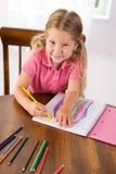 Edukacja: Ślicznej dziewczyny Rysunkowa tęcza Przy stołem Z Barwionym Penci obrazy royalty free