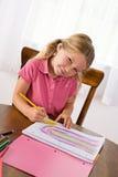 Edukacja: Ślicznej dziewczyny Rysunkowa tęcza Przy stołem Z Barwionym Penci obrazy stock