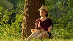 Edukacja i biznes Dziewczyny obsiadanie w parku pod zielonym drzewem i działaniu na pastylce zbiory wideo