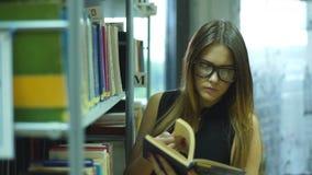 Edukacja i szkoły pojęcie - szczęśliwa studencka dziewczyna lub młoda kobieta z książką w bibliotece zdjęcie wideo