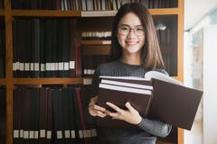 Edukacja najpierw, Piękny żeński student collegu trzyma jej bo zdjęcie royalty free