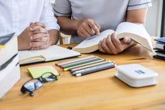 Edukacja, nauczanie, uczenie pojęcie Szkoła średnia koledzy z klasy lub ucznie grupują adiunkta w bibliotecznym studiowaniu i czy obraz stock