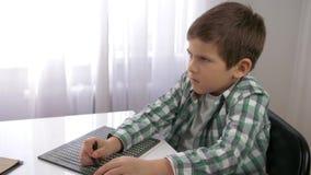 Edukacja Wzrokowo nadwyrężeni dzieci, niewidomy dziecko chłopiec uczenie pisać symbol chrzcielnicy brajlu obsiadaniu przy stołem  zdjęcie wideo