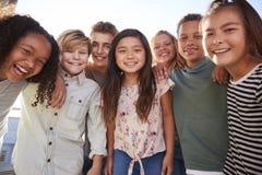 Eduque as crianças que penduram para fora durante a ruptura, sorrindo à câmera fotos de stock