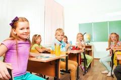 Eduque as crianças que sentam-se em estudar mesas na classe Fotos de Stock