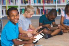 Eduque as crianças que sentam-se no assoalho usando a tabuleta digital na biblioteca fotos de stock royalty free