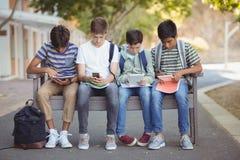 Eduque as crianças que usam o telefone celular e a tabuleta digital no banco imagens de stock