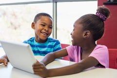 Eduque as crianças que usam uma tabuleta digital na sala de aula fotos de stock