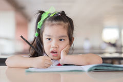 eduque a criança que pensa sobre a resposta que senta-se em sua mesa imagem de stock