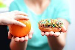 Eduque crianças para escolher o conceito saudável do alimento com escolha da menina comer o fruto, não uma filhós foto de stock