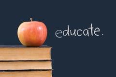 Eduque en la pizarra con la manzana y los libros Imagenes de archivo