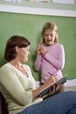 Eduque a menina e o professor pelo quadro-negro na sala de aula Foto de Stock Royalty Free