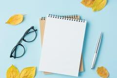 eduque o caderno em um fundo azul com folhas de outono Fotos de Stock Royalty Free