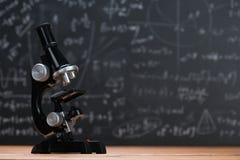 Eduque o microscópio em uma madeira e em um fundo do quadro fotografia de stock