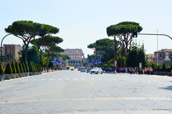 Ee-lined street via dei Fori Imperiali with view of Coliseum with traffic cars in Rome city in spring. ROME, ITALY - APRIL 4, 2016: tree-lined street via dei Stock Photo