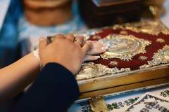 Eed bij de jonggehuwden op luxuriously verfraaide bijbel, handen van mannen en vrouwen in de kerk dichtbij het altaar royalty-vrije stock fotografie