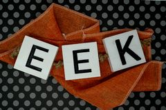 Eek Halloween phrase letters on orange fabric with fun black pol. Ka dot background. Useful for Halloween projects and headers royalty free stock image
