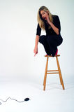 Eek! A Mouse!. Young woman on a stool afraid of a computer mouse Stock Photo