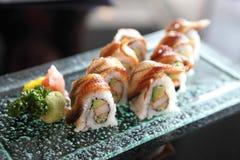 Eel and avocado maki sushi, Japanese food. Eel and avocado maki sushi on a glass plate stock image