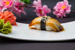 Eel sushi nigiri. On white plate with ginger and wasabi decorated with sakura royalty free stock photo