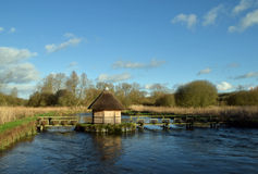 Eel Traps on the River Test Hampshire UK. Eel traps and a small thatched roof hut on the River Test, Hampshire on a sunny winters day Stock Image