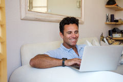 Eelaxed middle aged man smiling with laptop at home. Portrait of a relaxed middle aged man smiling with laptop at home Royalty Free Stock Image