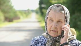 Eelderly kvinnasamtal genom att använda smartphonen utomhus arkivfilmer