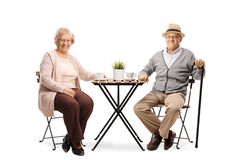 Eelderly woman and elderly man sitting at a table with a cup of coffee and smiling at the camera stock photography