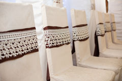 Eelegantly decorated white wedding chairs with brown ribbons at Royalty Free Stock Photos