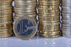 Een één euro muntstuk voor veel meer die muntstukken in kolommen o worden gestapeld stock afbeeldingen
