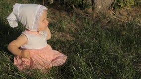 Een éénjarig oud babymeisje zit op het gras en slaat handen De heldere het plaatsen zon glanst net in haar gezicht stock footage