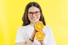 Een 13-14 éénjarigenmeisje in de handen die sinaasappelen houden Royalty-vrije Stock Fotografie